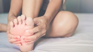 Person on bed holding foot due to pains caused by gout