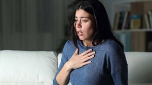 Woman with hand on chest having a panic attack