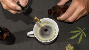 CBD oil being dropped in a cup of coffee with CBD hemp leaf on the table