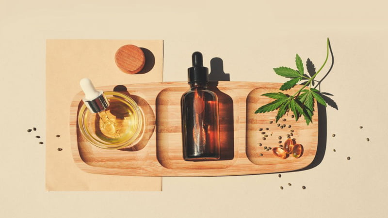 CBD Oil in the Wooden Tray with Hemp Leaves