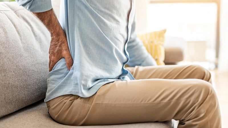 a man having lower back pain while sitting on a couch