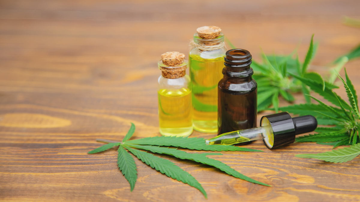 CBD Oil with Hemp Leaves in Wooden Surface