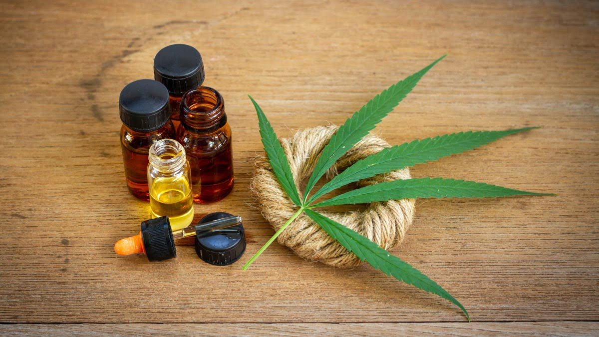 CBD Oil Bottles with Hemp Leaf and Rope on the Wooden Surface