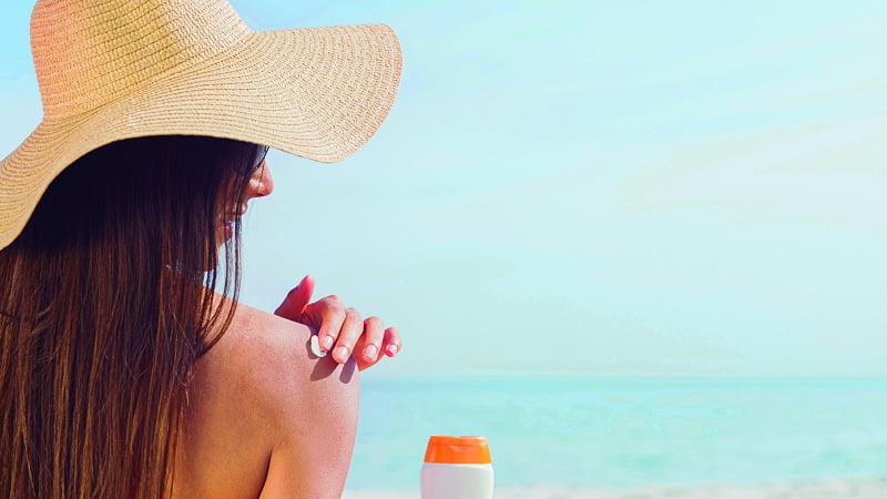 a woman at the beach applying CBD sunscreen onto her own shoulder