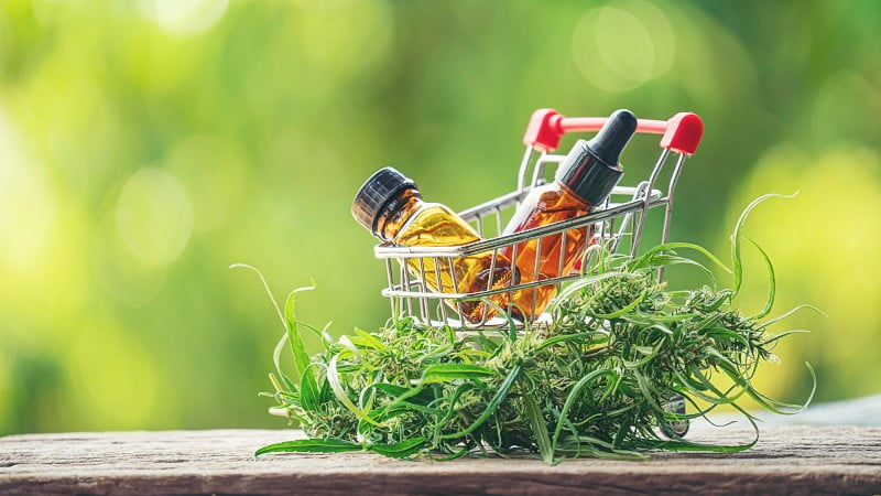 hemp leaves and Delta 8 THC extract in bottles on a cart