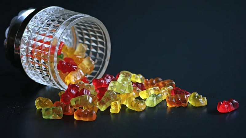 multicolored D8 THC gummies in a bowl on a black background