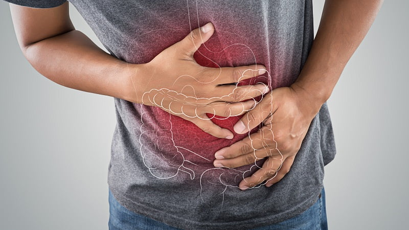 image of stomach and large intestine illustration on a man's body against gray background